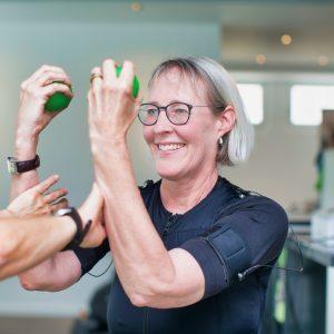 Frau fortgeschrittenen Alters beim EMS-Training mit persönlichem Coach
