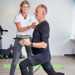 Mann fortgeschrittenem Alters beim EMS-Training mit persönlichem Coach